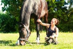 Seduta equestre della giovane donna vicino al suo cavallo su erba fotografia stock