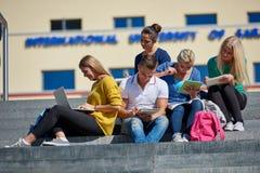 Seduta esterna degli studenti sui punti Immagini Stock