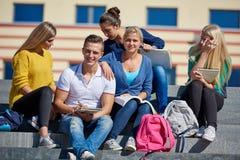 Seduta esterna degli studenti sui punti Fotografia Stock Libera da Diritti
