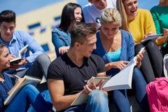 Seduta esterna degli studenti sui punti Fotografia Stock