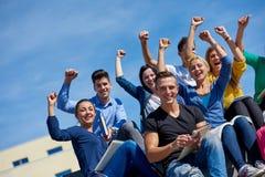 Seduta esterna degli studenti sui punti Immagine Stock