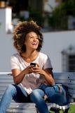 Seduta femminile afroamericana attraente con il telefono cellulare e la risata Immagine Stock