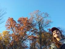 Seduta femminile al parco il giorno perfetto dell'autunno fotografia stock libera da diritti
