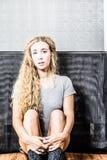 Seduta femminile americana sveglia sul pavimento Fotografia Stock