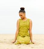 Seduta femminile attraente alla spiaggia ed a meditare Immagini Stock Libere da Diritti