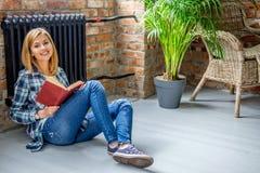 Seduta femminile bionda sul pavimento e sulla lettura un libro Fotografia Stock