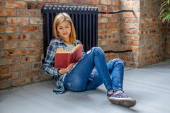 Seduta femminile bionda sul pavimento e sulla lettura un libro Fotografie Stock