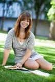 Seduta femminile con il libro su erba Fotografia Stock Libera da Diritti