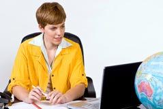 Seduta femminile dietro uno scrittorio in rivestimento luminoso e giallo. Fotografia Stock Libera da Diritti