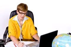 Seduta femminile dietro uno scrittorio in rivestimento luminoso e giallo Immagini Stock Libere da Diritti