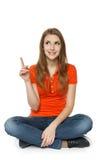 Femmina che si siede sul pavimento, indicante su Immagine Stock