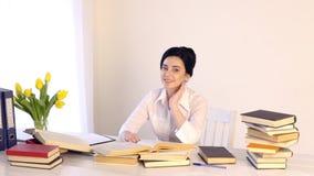 Seduta femminile nel suo luogo di lavoro e ridere mentre leggendo tenendo libro stock footage