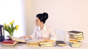 Seduta femminile nel suo luogo di lavoro e ridere mentre leggendo tenendo libro video d archivio