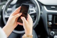 Seduta femminile nell'automobile e nel mandare un sms Immagini Stock