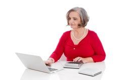 Seduta femminile senior attraente della mangiatoia isolata sullo scrittorio con il co immagine stock