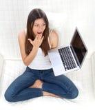 Seduta femminile sorpresa con il computer portatile moderno Fotografia Stock Libera da Diritti