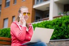 Seduta femminile sul banco e sul computer portatile e sullo smartphone usando Immagine Stock