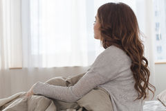 Seduta femminile sul letto nella vista della parte posteriore di mattina Immagine Stock Libera da Diritti