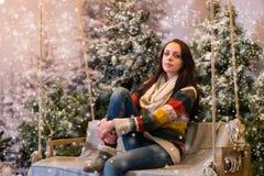 Seduta femminile sveglia su un banco o un'oscillazione con una coperta in uno Sn Immagine Stock Libera da Diritti