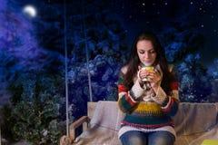 Seduta femminile sveglia su un'oscillazione con una coperta e una tenuta un la tazza Immagini Stock