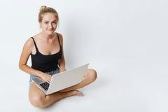Seduta femminile sveglia sul pavimento con le gambe attraversate, facendo uso del computer portatile per la ricerca informazioni  Immagine Stock