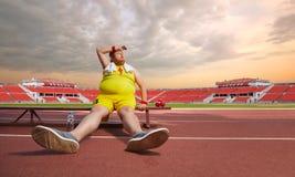 Seduta grassa dell'uomo stanca sulla pista dello stadio fotografia stock libera da diritti