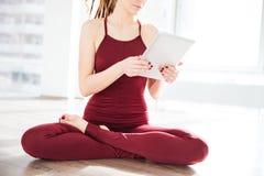 Seduta graziosa del ballerino della giovane donna e compressa usando Immagini Stock