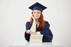 Seduta laureata della bella femmina con sorridere dei libri Priorità bassa bianca Copi lo spazio Fotografia Stock Libera da Diritti