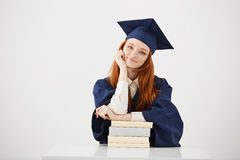 Seduta laureata della bella femmina con sorridere dei libri Priorità bassa bianca Copi lo spazio Immagine Stock