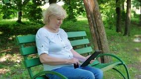 Seduta online dell'affare anziano della donna sul banco nel parco Acquisto femminile senior tramite computer della compressa di u video d archivio