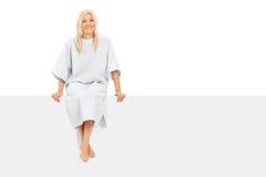 Seduta paziente femminile su un'insegna in bianco Immagini Stock