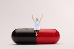 Seduta paziente matura su una pillola gigante Fotografia Stock Libera da Diritti