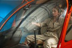 Seduta pilota della donna attraente nell'elicottero fotografia stock