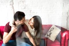 Seduta rilassata delle giovani coppie felici a casa sullo strato immagini stock libere da diritti