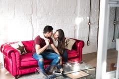 Seduta rilassata delle giovani coppie felici a casa sullo strato fotografia stock libera da diritti