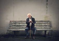 Seduta senior su un banco Immagini Stock