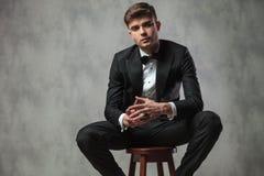 Seduta sexy dell'uomo d'affari mentre tenendo le dita insieme Fotografia Stock