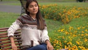 Seduta sola teenager femminile ispana sul banco di parco video d archivio