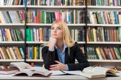 Seduta sorridente ad uno scrittorio nella biblioteca con una nota aperta Immagine Stock Libera da Diritti