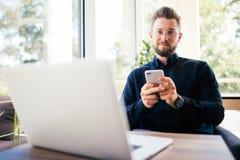 Seduta sorridente del giovane uomo d'affari felice nell'ufficio con il computer portatile mentre leggendo il suo smartphone Ritra Fotografie Stock