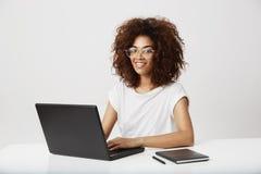 Seduta sorridente della bella ragazza africana con il computer portatile nel luogo di lavoro Priorità bassa bianca Immagine Stock Libera da Diritti