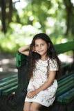 Seduta sorridente della bella ragazza sul banco nel parco Fotografie Stock
