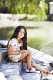 Seduta sorridente della bella ragazza sulle scale nel parco Fotografia Stock Libera da Diritti