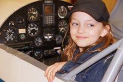 Seduta sorridente della ragazza nella cabina di pilotaggio dell'aeroplano immagini stock