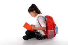 Seduta sorridente latina del manuale o del blocco note della lettura del bambino sul pavimento Fotografia Stock