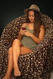 Seduta teenager e mandare un sms Immagini Stock