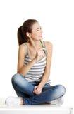 Seduta teenager femminile di Joyfull su una tabella. Immagini Stock