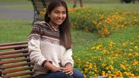 Seduta teenager ispanica felice di Latina nel parco video d archivio