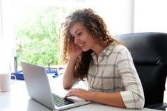 Seduta teenager sorridente allo scrittorio con il computer portatile Fotografia Stock
