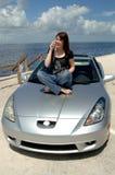 Seduta teenager sul cappuccio dell'automobile sul telefono delle cellule Immagini Stock